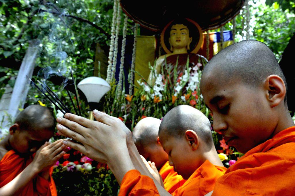 Bengaluru: Buddhist monks offer prayers at a temple on Buddha Purnima, in Bengaluru, on May 4, 2015.