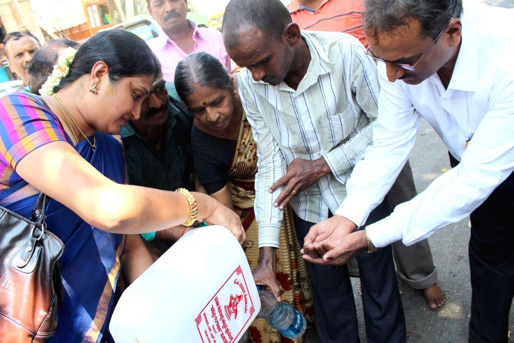 Bengaluru: Devotees distribute Gangajal on the occasion of Mahashivaratri, at Rameshwara Swamy Temple in Bengaluru, on Feb 17, 2015. 40000 liters of Gangajal was distributed.