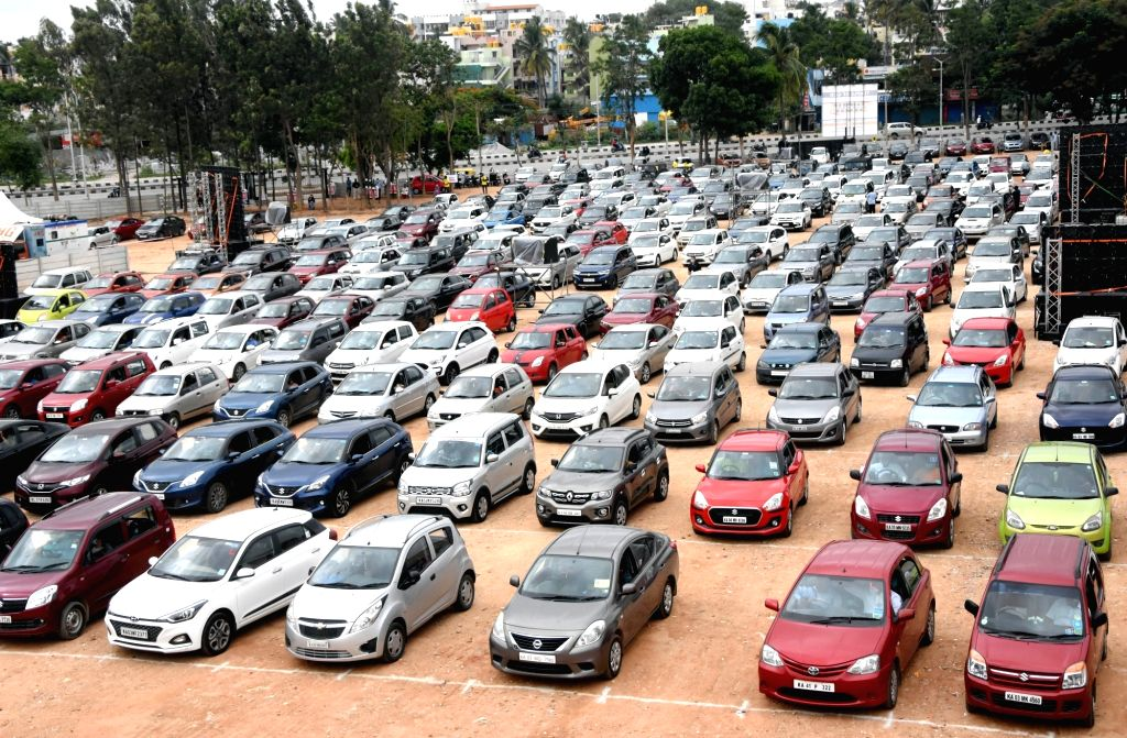 Bengaluru: Bengaluru: Members of a Church, adhering to social distancing norms, sing and pray while sitting in their cars after parking them on ground during  drive-in worship,amid the ongoing COVID-19 lockdown, in Bengaluru, on June 14, 2020. (Photo