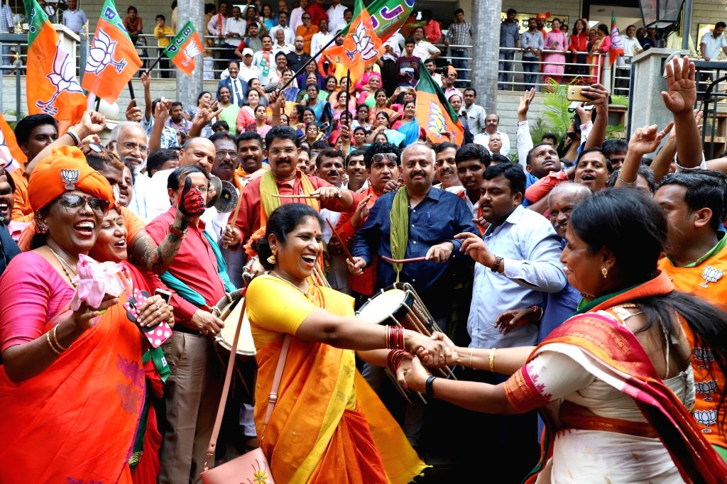 Bengaluru: BJP workers celebrate as the party led by Prime Minister Narendra Modi is set to retain power for another five years after making a sweep of the 2019 Lok Sabha battle and mauling the opposition; in Bengaluru on May 23, 2019. (Photo: IANS) - Narendra Modi
