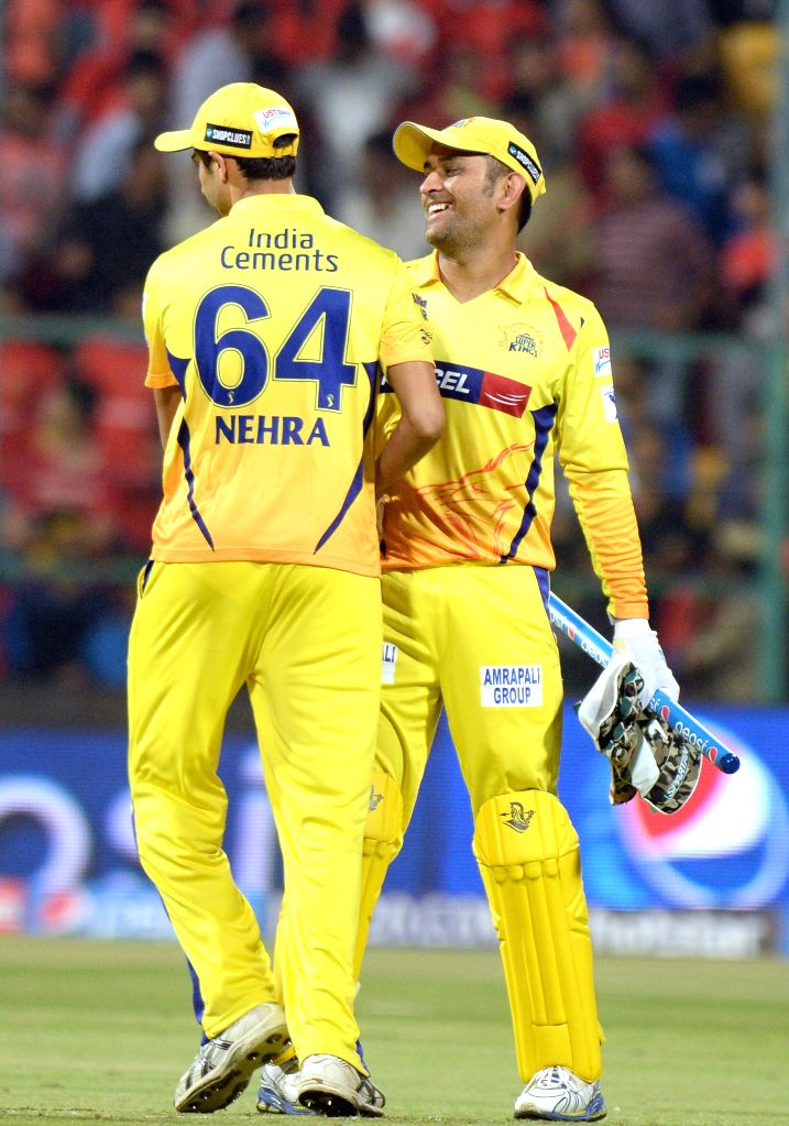 Chennai Super Kings players Ashish Nehra and MS Dhoni celebrate fall of a wicket during an IPL-2015 match between Royal Challengers Bangalore and Chennai Super Kings at M Chinnaswamy ... - Ashish Nehra and MS Dhoni