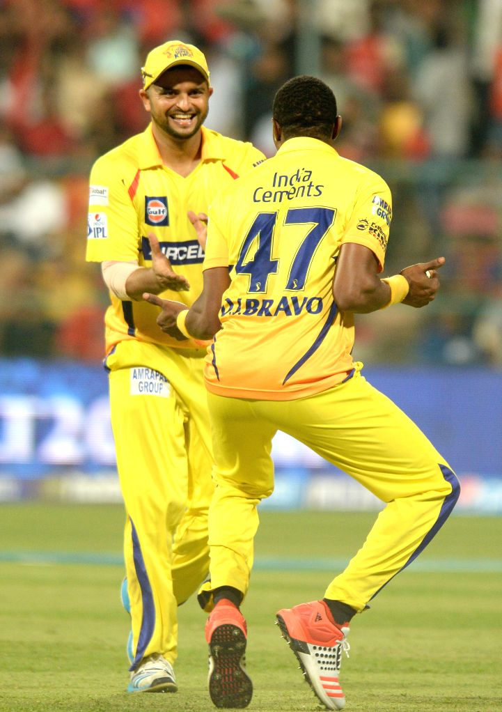 Chennai Super Kings players Suresh Raina and Dwayne Bravo  celebrate fall of a wicket during an IPL-2015 match between Royal Challengers Bangalore and Chennai Super Kings at M Chinnaswamy ...