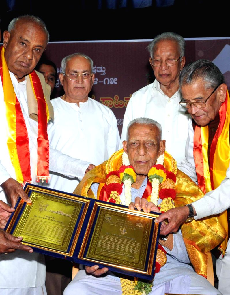 Former prime minister and JD (S) chief H D Deve Gowda felicitates freedom fighter HS Doreswamy during Kengal Hanumantaiah award presentation ceremony in Bengaluru, on Feb 8, 2015.