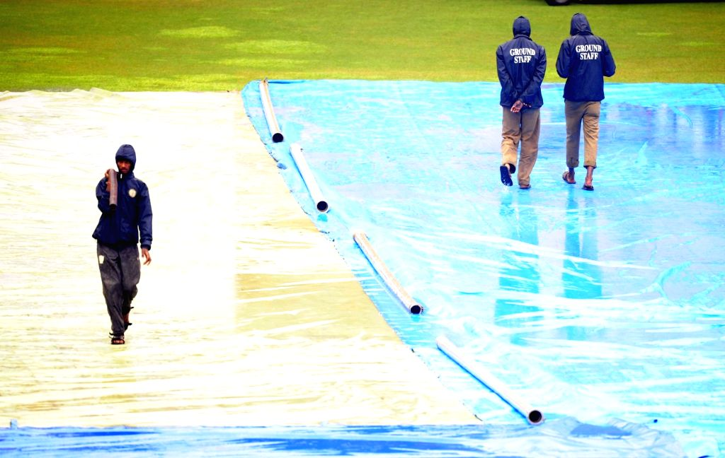 : Bengaluru: Groundsmen cover the pitch with tarpaulin sheets as rain delay the start of the 2nd day of the second test match between India and South Africa at M Chinnaswamy Stadium in Bengaluru, on ...