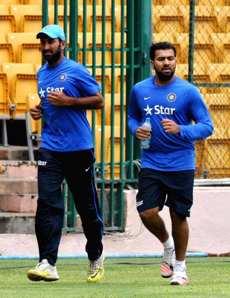 : Bengaluru: Indian cricketers Cheteshwar Pujara and Rohit Sharma during a practice session ahead of the 2nd test match against South Africa at Chinnaswamy Stadium, in Bengaluru on Nov. 12, 2015. ... - Cheteshwar Pujara