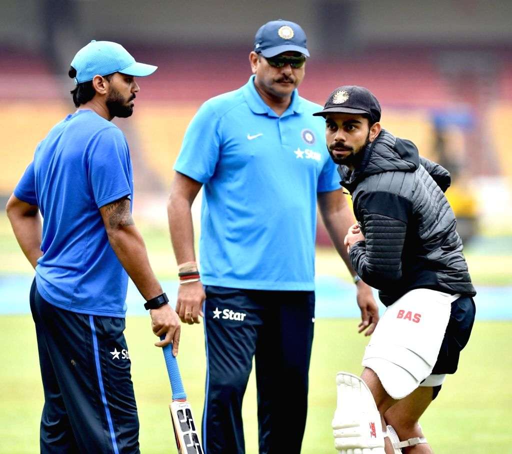 :Bengaluru: Indian cricketers Virat Kohli, Murali Vijay and team director Ravi Shastri during a practice session ahead of the 2nd test match against South Africa at Chinnaswamy Stadium, in ...