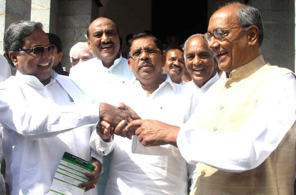 Karnataka Chief Minister K Siddaramaiah and MLC G Parmeshwar greeting AICC General Secretary Digvijaya Singh in Bengaluru on Jan. 24, 2015. - Secretary Digvijaya Singh