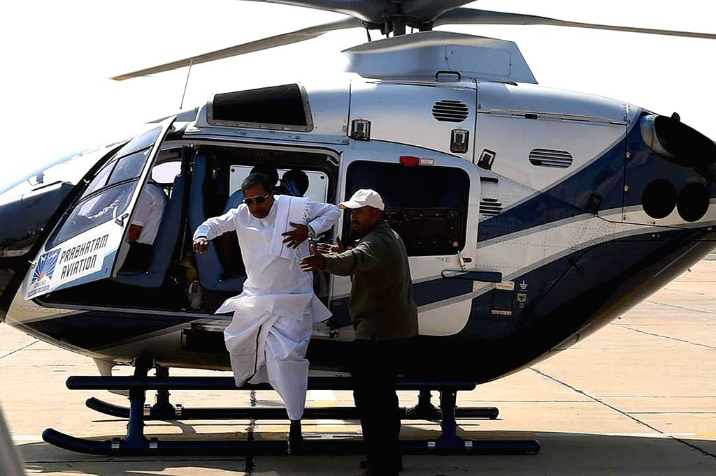 Karnataka Chief Minister Siddaramaiah deboards a helicopter after a fire broke out in its silencer in Bengaluru on Jan 10, 2015. The chief minister and 3 others were evacuated unhurt. - Siddaramaiah
