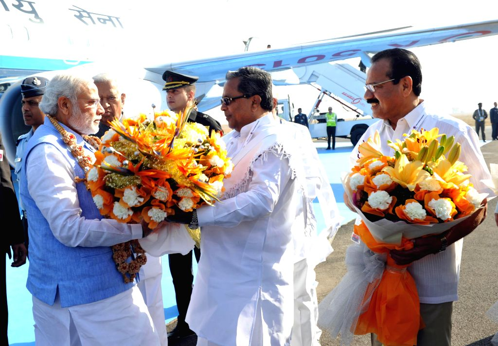 Karnataka Chief Minister Siddaramaiah receives Prime Minister Narendra Modi on his arrival at Yelahanka Air-force Station, in Bengaluru on Feb 18, 2015. Also seen Union Minister for Law ... - Siddaramaiah and Narendra Modi