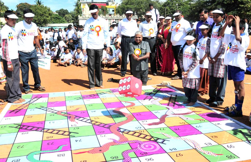 Karnataka Commissioner for Persons with Disabilities K   S Rajanna plays  a game of  snakes and ladders   with children during  `CBM Include Vidya Abhiyan - 2014` ..