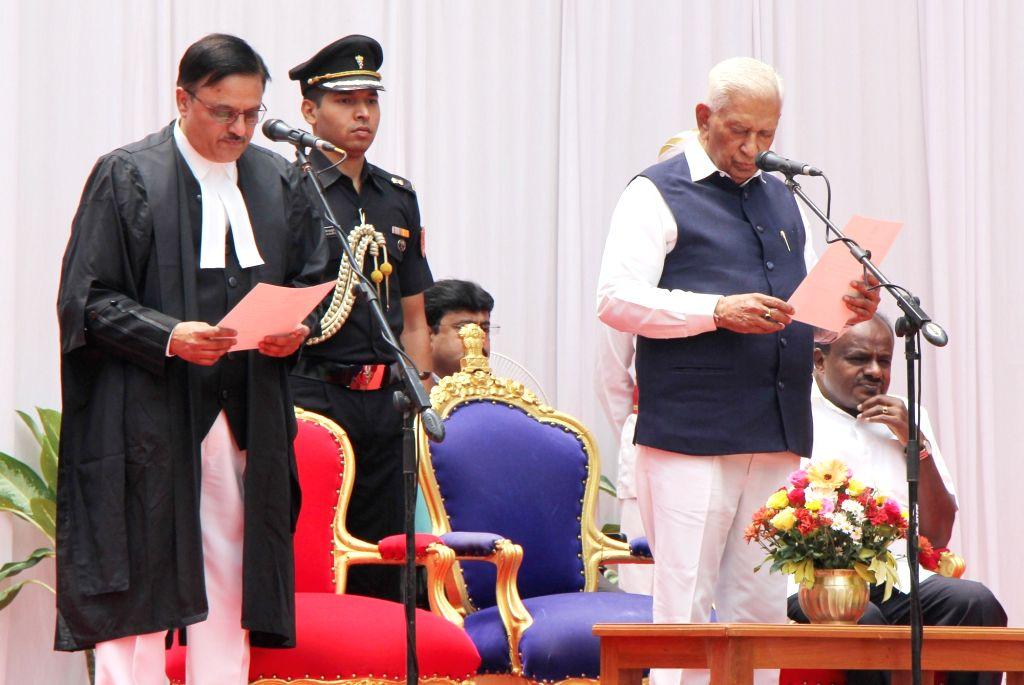Bengaluru: Karnataka Governor Vajubhai Rudabhai Vala administers the oath of office to Justice Abhay Shreeniwas Oka as the new Chief Justice of Karnataka High Court, in Bengaluru, on May 10, 2019. Also seen Chief Minister HD Kumaraswamy. (Photo: IANS - H