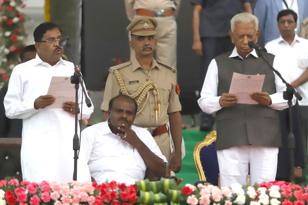 Bengaluru: Karnataka Governor Vajubhai Vala administers the oath of office to Congress leader G. Parameshwara, during a swearing-in ceremony at Vidhana Soudha in Bengaluru on May 23, 2018. ...