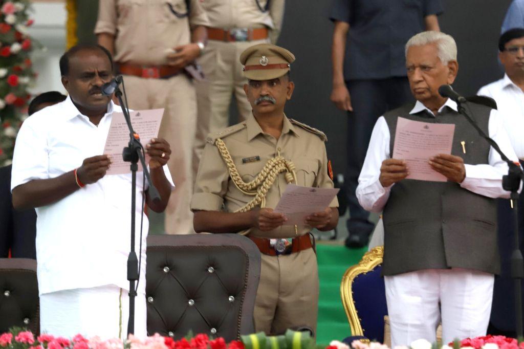 :Bengaluru: Karnataka Governor Vajubhai Vala administers the oath of office to Janata Dal-Secular (JD-S) leader H.D. Kumaraswamy at Vidhana Soudha in Bengaluru on May 23, 2018. Kumaraswamy was ...