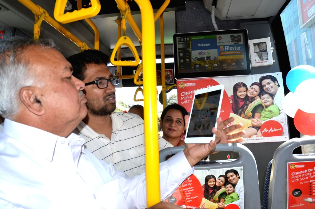 Karnataka Transport Minister Ramalinga Reddy uses the `Easy Travel Information Planner` - a mobile application aboard a BMTC bus, in Bengaluru on Jan 12, 2015. - Ramalinga Reddy