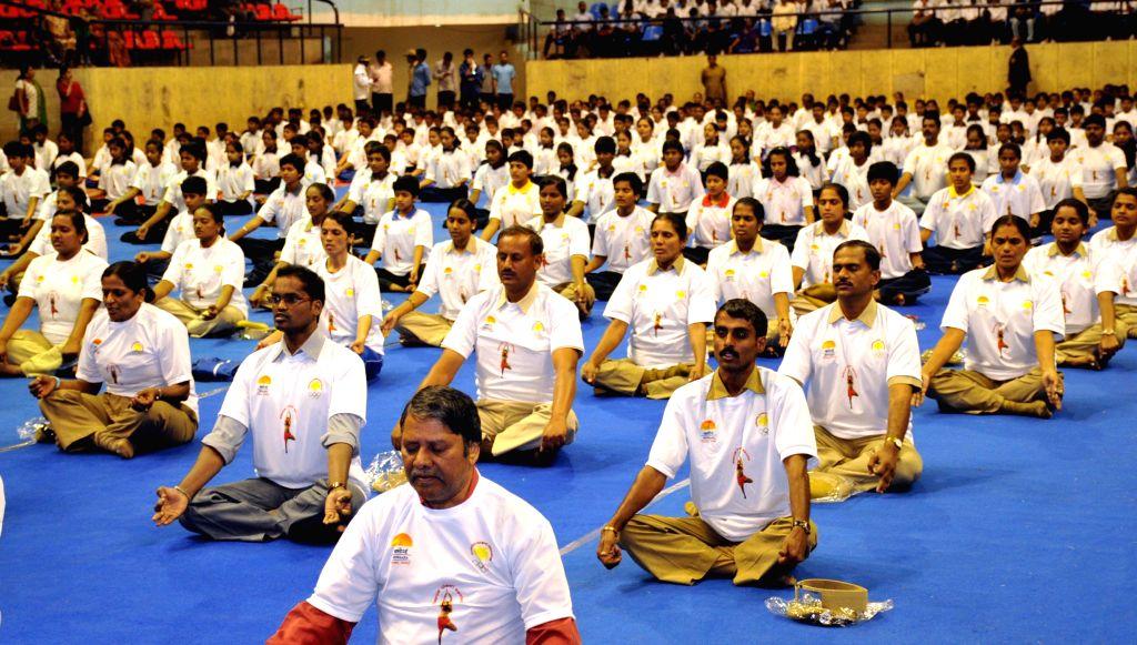 Participant`s perform yoga during Karnataka Yoga Abhiyana Camp, organised by Karnataka Olympics Association, at Kanteerva Indoor Stadium, in Bengaluru on Jan 10, 2015.