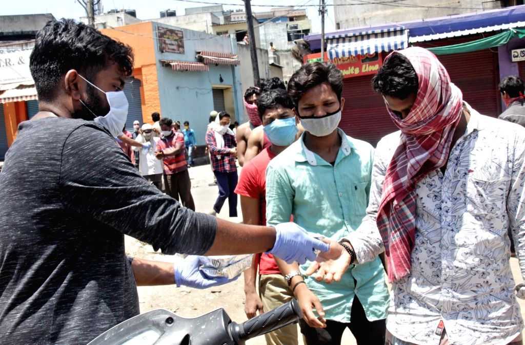 Bengaluru: People being offered hand sanitiser as they queue up to collect food during free food distribution on Day 6 of the 21-day countrywide lockdown imposed to contain the spread of novel coronavirus, in Bengaluru on March 30, 2020. (Photo: IANS
