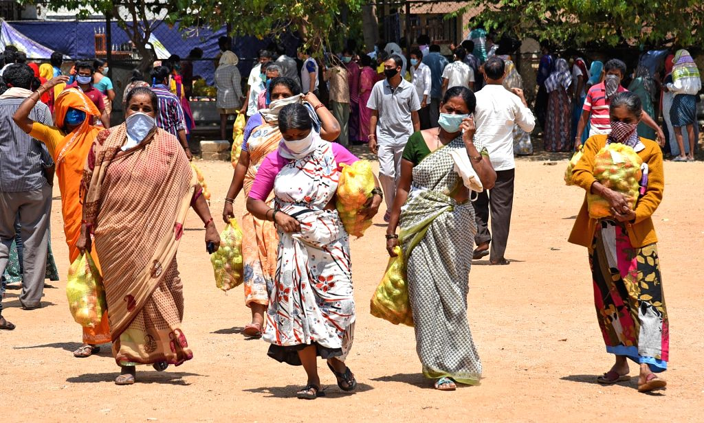 Bengaluru: People stand in queues to collect vegetables being distributed free of cost among the poor, needy and homeless people in Bengaluru during the extended nationwide lockdown imposed to mitigate the spread of coronavirus; on Apr 23, 2020. (Pho