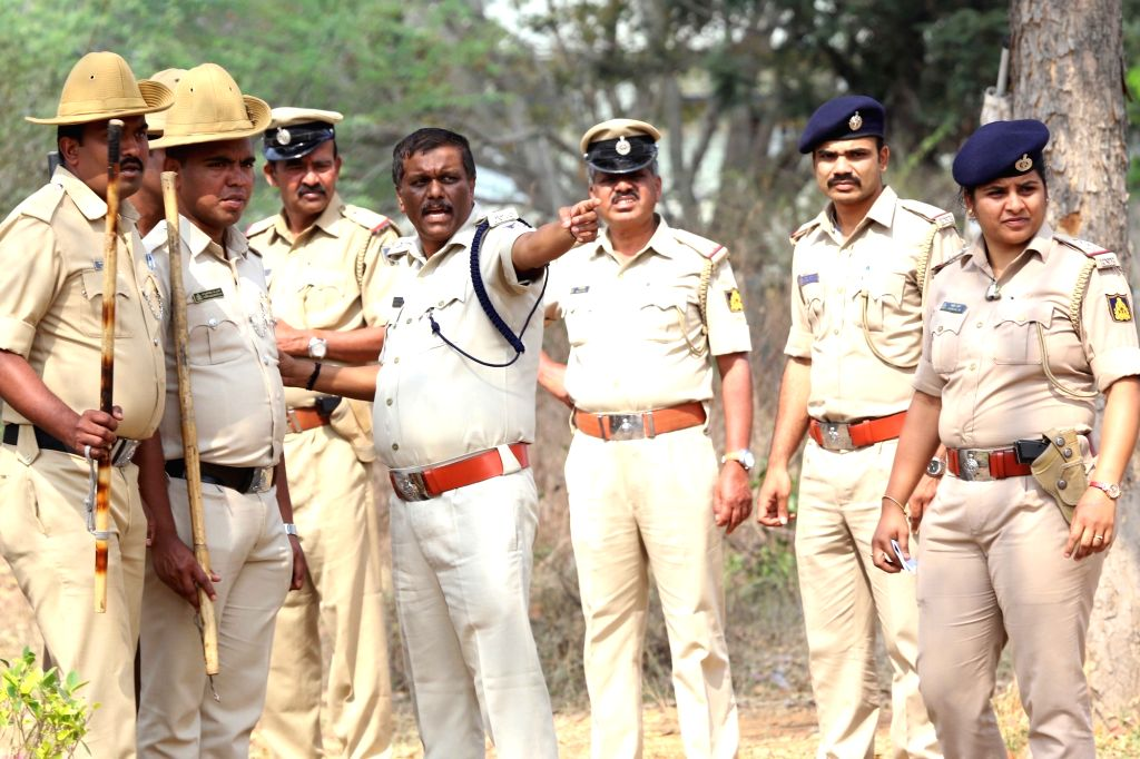 Bengaluru: Police personnel at the site where Hawk MK 132 aircraft of Indian Air Force's Surya Kiran display team crashed after a mid-air collision while rehearsing for upcoming  'Aero ...