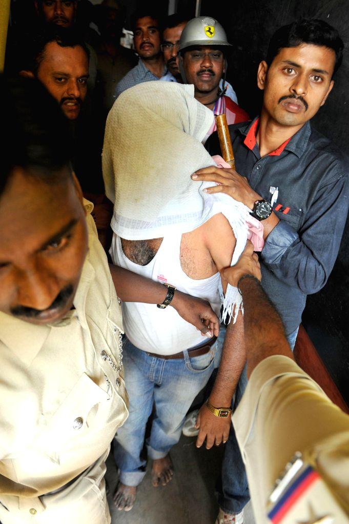 Policemen arrest the school teacher who allegedly molested a minor in Bengaluru, on Jan 7, 2015.