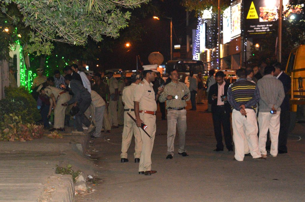 Policemen at the site of the low intensity bomb blast that rocked Church Street area of Bengaluru on Dec 28, 2014. Two people, including a woman, were injured in the blast near a food ...