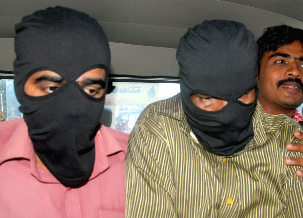 :Bengaluru: Policemen take away the two security guards allegedly involved in the gang-rape of a 30-year-old woman at Cubbon Park in Bengaluru on Nov. 12, 2015. (Photo: IANS).