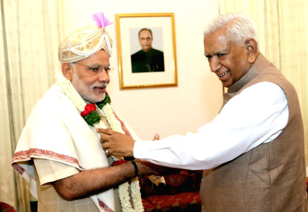 Prime Minister Narrendra Modi being felicitated by Karnataka Governor Vajubhai Rudabhai Vala at Raj Bhavan, in Bengaluru, on April 4, 2015. - Narrendra Modi