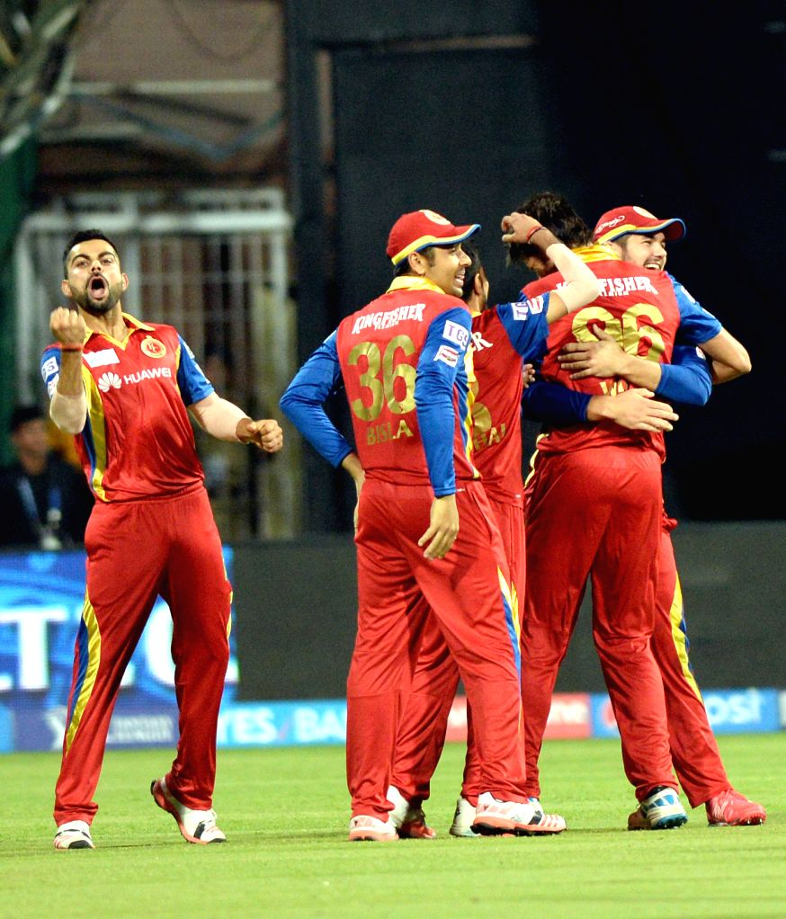 Royal Challengers Bangalore players celebrate fall of a wicket during an IPL-2015 match between Royal Challengers Bangalore and Mumbai Indians at M Chinnaswamy Stadium, in Bengaluru, on ...