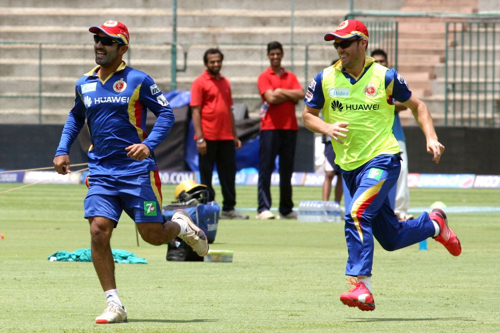 Royal Challengers Bangalore players Dinesh Karthik and AB de Villiers during a practice session at M Chinnaswamy Stadium, in Bengaluru, on May 1, 2015.