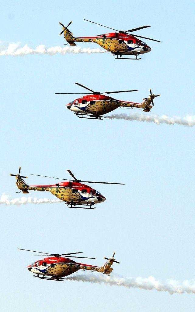 Sarang helicopters perform aerobatics during the Aero India-2015 Air Show, at Yelahanka Air-force Station, in Bengaluru on Feb 21, 2015.