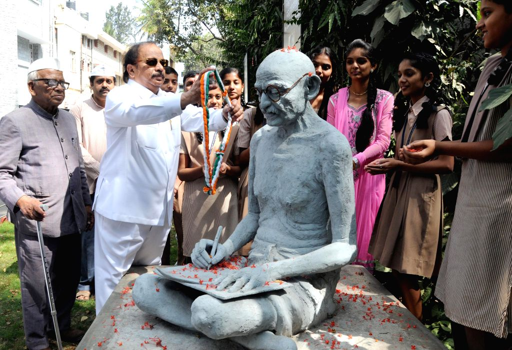 Students offering floral tribute to Mahatma Gandhi Statue on the occasion of Martyr's Day in Bengaluru on Jan. 30, 2015. - Gandhi Statue