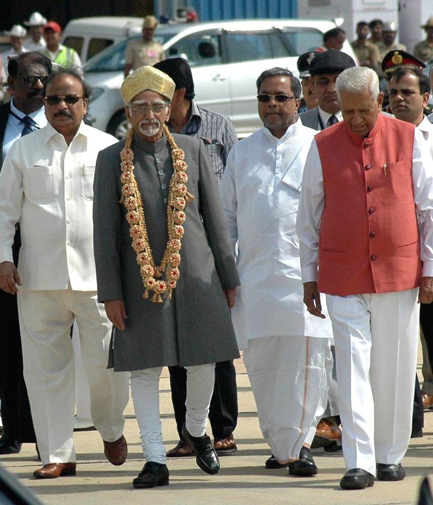 Vice President Mohd. Hamid Ansari being received by the Chief Minister of Karnataka Siddaramaiah and Governor of Karnataka Vajubhai Rudabhai Vala on his arrival at the HAL airport, ...