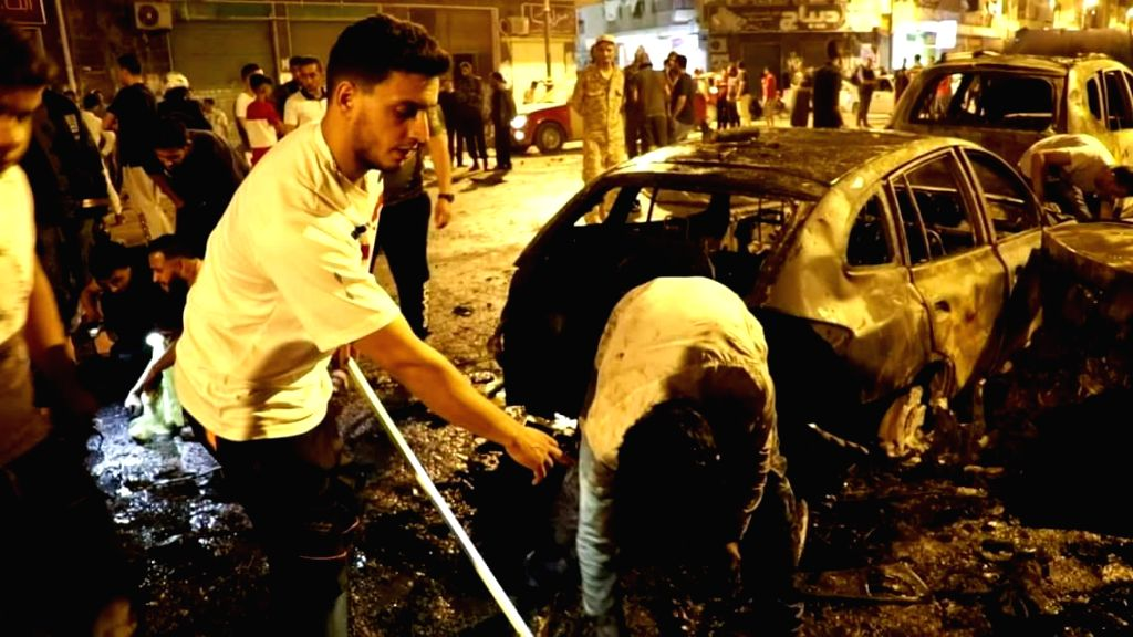 BENGHAZI, May 25, 2018 - People check destoryed vehicles in the eastern Libyan city of Benghazi, Libya, on May 25, 2018. A car bomb explosion killed six and injured more than 20 people in the eastern ...
