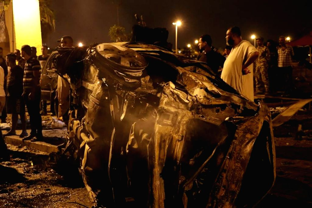 BENGHAZI, May 25, 2018 - People gather around a destoryed vehicles in the eastern Libyan city of Benghazi, Libya, on May 25, 2018. A car bomb explosion killed six and injured more than 20 people in ...