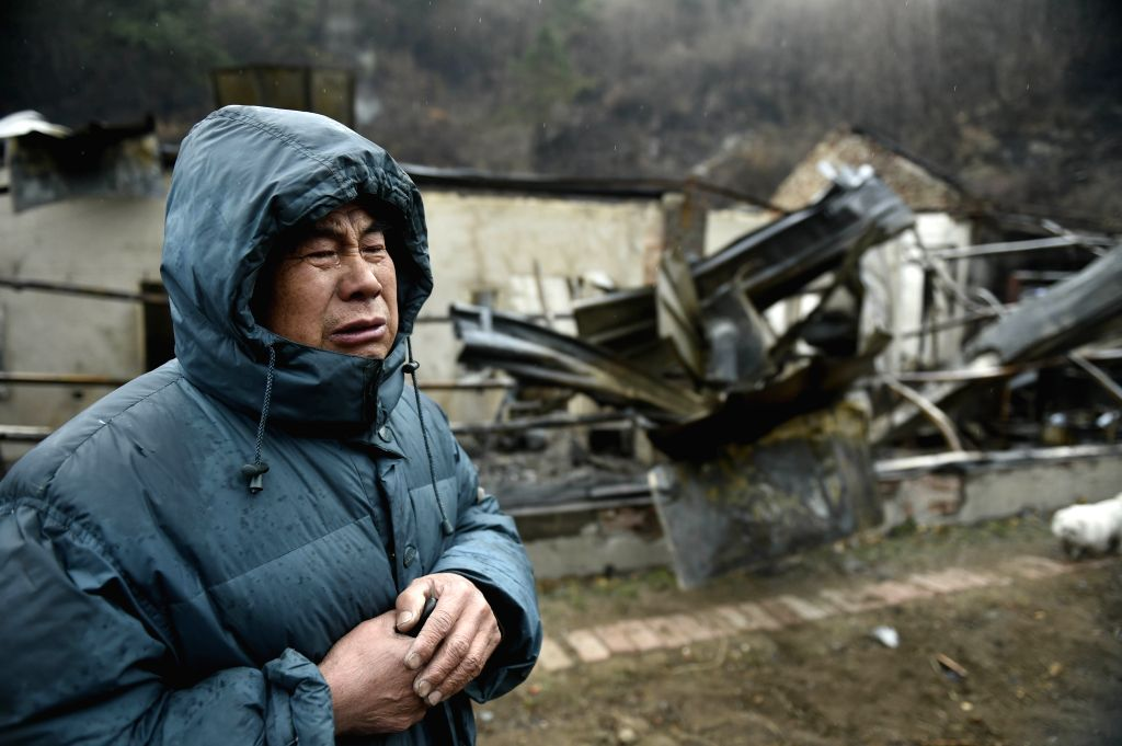 BENXI, April 12, 2016 - Yu Bin, a local farmer, cries as talking about his house damaged by a fire on Xiaosonggou Mountain in Benxi City, northeast China's Liaoning Province, April 12, 2016. Several ...