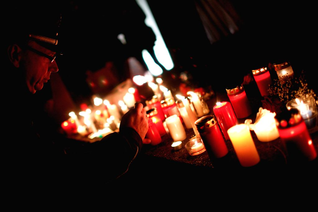 A policeman lights a candle during a memorial activity for the Crystal Night at Berlin's Grunewald train station in Berlin, Germany, on Nov. 7, 2014. Some 100 middle school students and ...