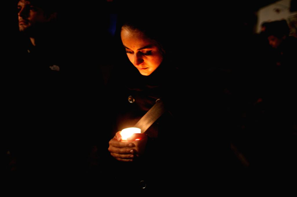 A woman holding a candle takes part in a memorial activity for the Crystal Night at Berlin's Grunewald train station in Berlin, Germany, on Nov. 7, 2014. Some 100 middle school students and ..