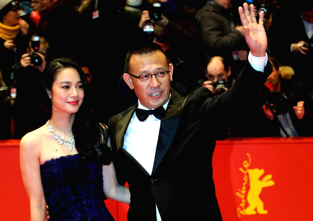 """Jiang Wen (R) and Zhou Yun pose for photos on the red carpet for the promotion of the movie """"Gone With The Bullets"""" (Yi Bu Zhi Yao) at the 65th Berlinale .."""