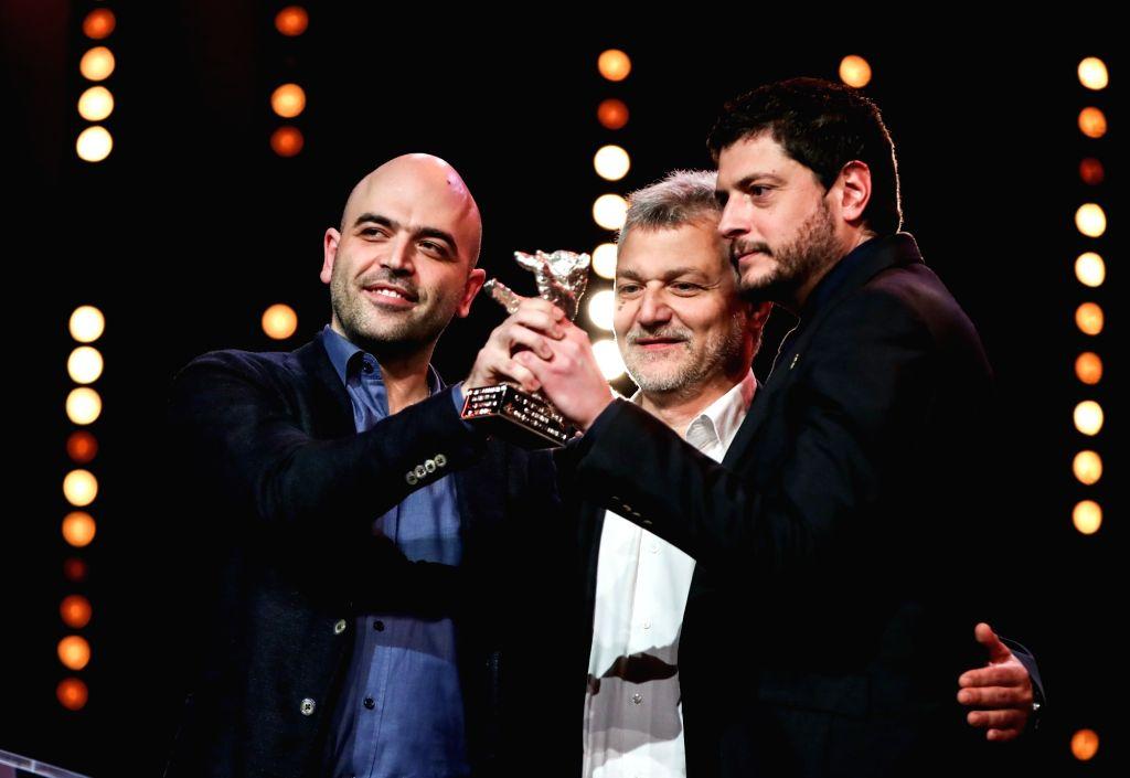 BERLIN, Feb. 17, 2019 - Director and screenwriter Claudio Giovannesi (R) and screenwriters Maurizio Braucci (C), Roberto Saviano receive the Silver Bear for Best Screenplay award for ...