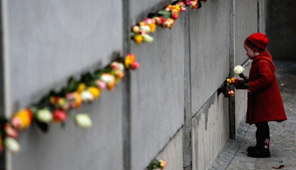 Berlin (Germany): A girl puts flowers into a part of the former Belrin Wall during a memorial activity to commemorate the 25th anniversary of the fall of the Berlin Wall in Berlin, Germany, on Nov. ..