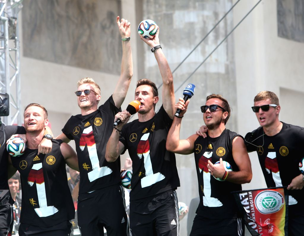 German football players Andre Schuerrle (L2), Miroslav Klose (C), Mario Goetze (R2) and Toni Kroos (R) wave to supporters during celebration to mark the team's 2014 .
