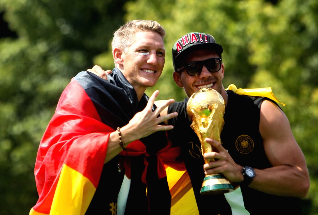 German football players Lukas Podolski (R) and Bastian Schweinsteiger pose during celebration to mark the team's 2014 Brazil World Cup victory in Berlin, Germany, ...