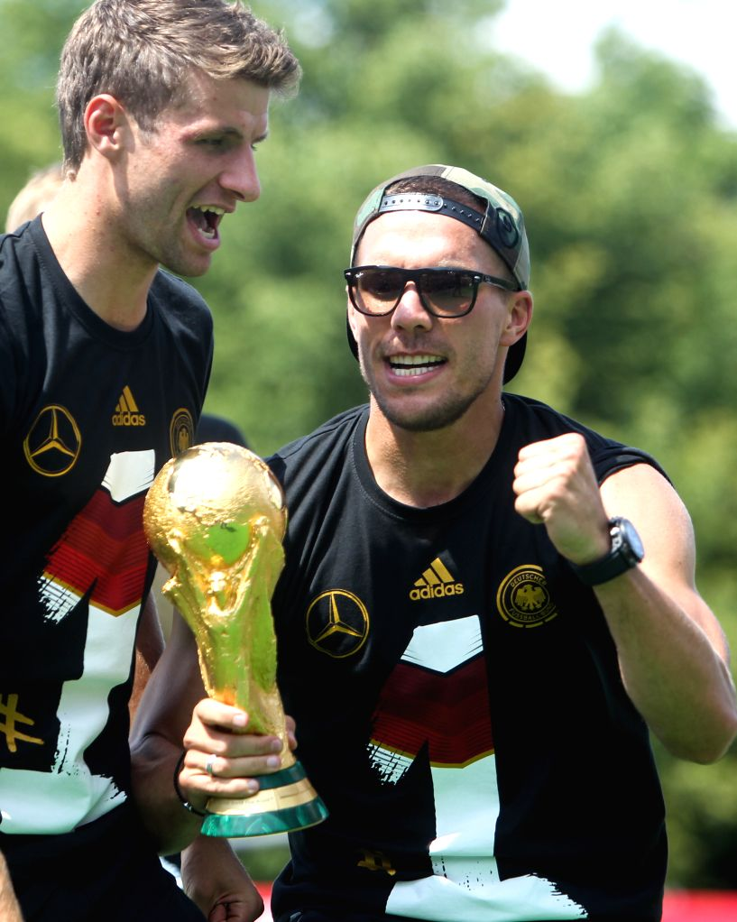 German football players Lukas Podolski (R) and Thomas Mueller celebrate on stage during celebration to mark the team's 2014 Brazil World Cup victory in Berlin, ...