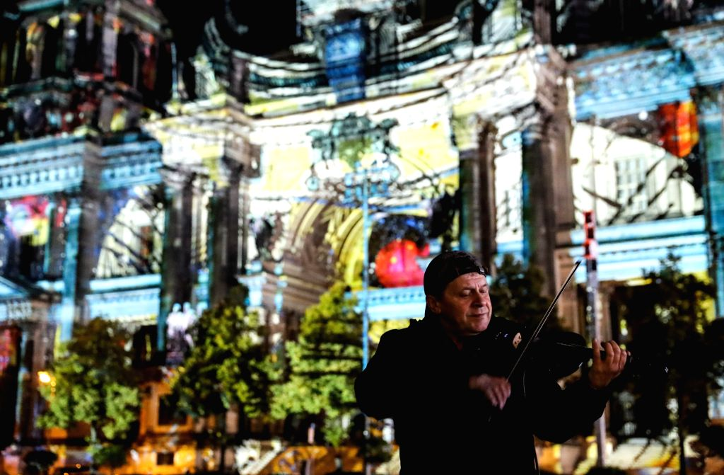 BERLIN, Oct. 8, 2016 - A performer plays violin in front of Berlin Cathedral during the Festival of Lights in Berlin, capital of Germany, on Oct. 7, 2016. Berlin turned into a city of light art with ...