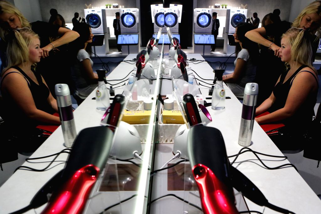 A visitor tries hairdressing devices at the booth of Panasonic during the 54th IFA consumer electronics fair in Berlin, Germany, on Sept. 5, 2014. The 54th IFA ...