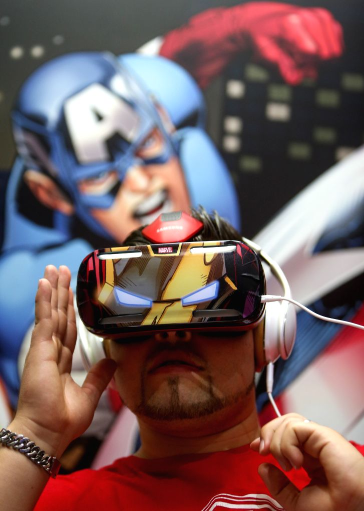 A visitor tries a Samsung Gear VR at Samsung's booth during the 54th IFA consumer electronics fair in Berlin, Germany, on Sept. 5, 2014. The 54th IFA consumer ...