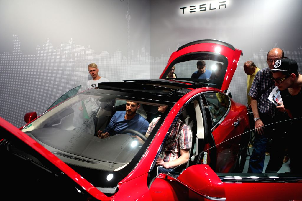 Visitors view a Tesla car during the 54th IFA consumer electronics fair in Berlin, Germany, on Sept. 5, 2014. The 54th IFA consumer electronics fair, Europe's ...