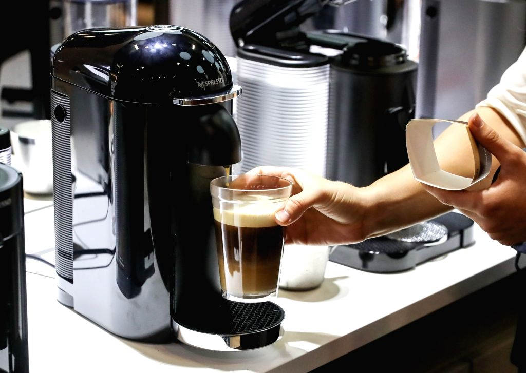 BERLIN, Sept. 5, 2018 - A working staff prepares a cup of coffee for a visitor at the booth of Nespresso during the 2018 IFA consumer electronics fair in Berlin, capital of Germany, on Sept. 5, 2018. ...
