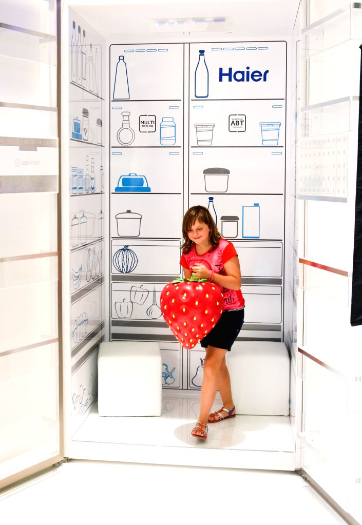 A girl poses for photos inside a giant refrigerator at Haier's booth during the 54th IFA consumer electronics fair in Berlin, Germany, on Sept. 6, 2014. More than ...