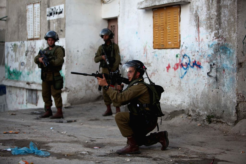 An Israeli soldier points his rifle at Palestinian protesters while confronting with them at the Aida refugee camp in the West Bank city of Bethlehem on April ...