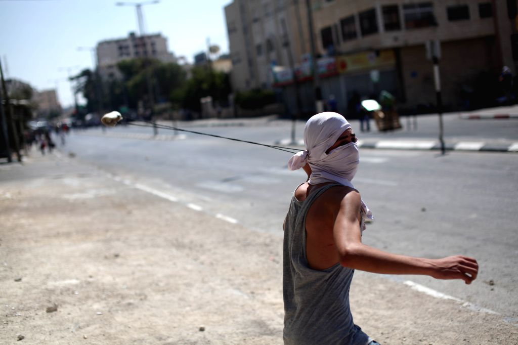 A Palestinian protester throws stones at Israeli soldiers during clashes following a demonstration against the Israeli offensive in the West Bank city of ...